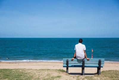 Person looking out at sea from atop a bench