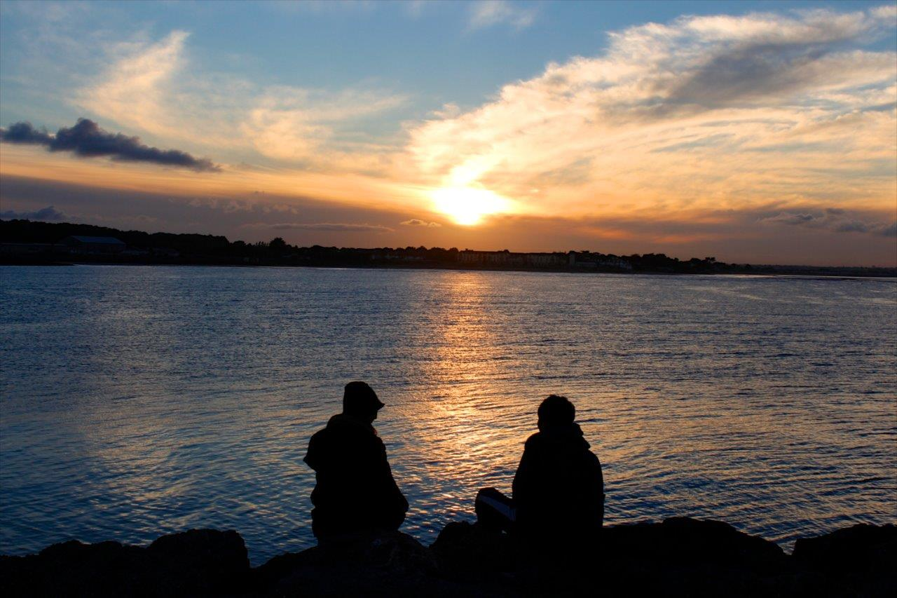 2 people sitting as the sun sets