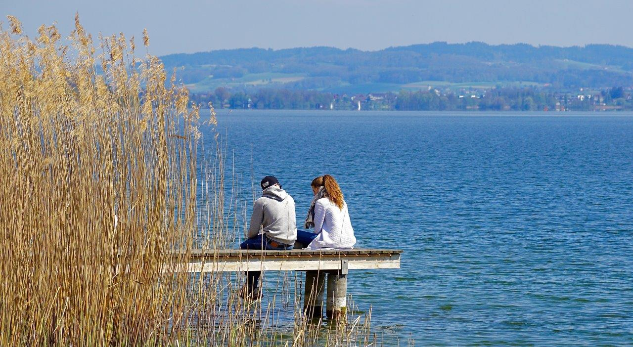 2 people sitting by water on pier