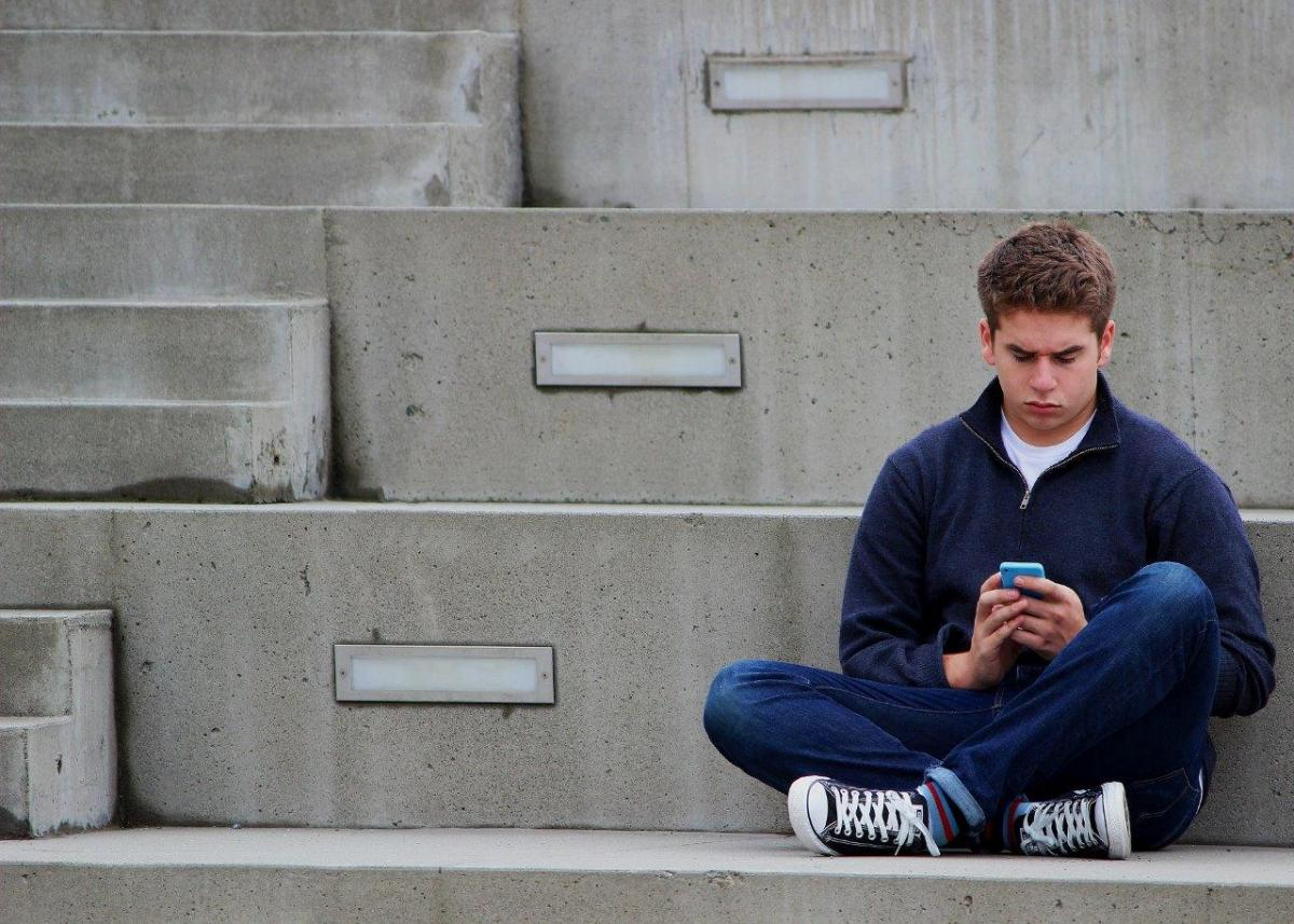 boy sat on ground texting
