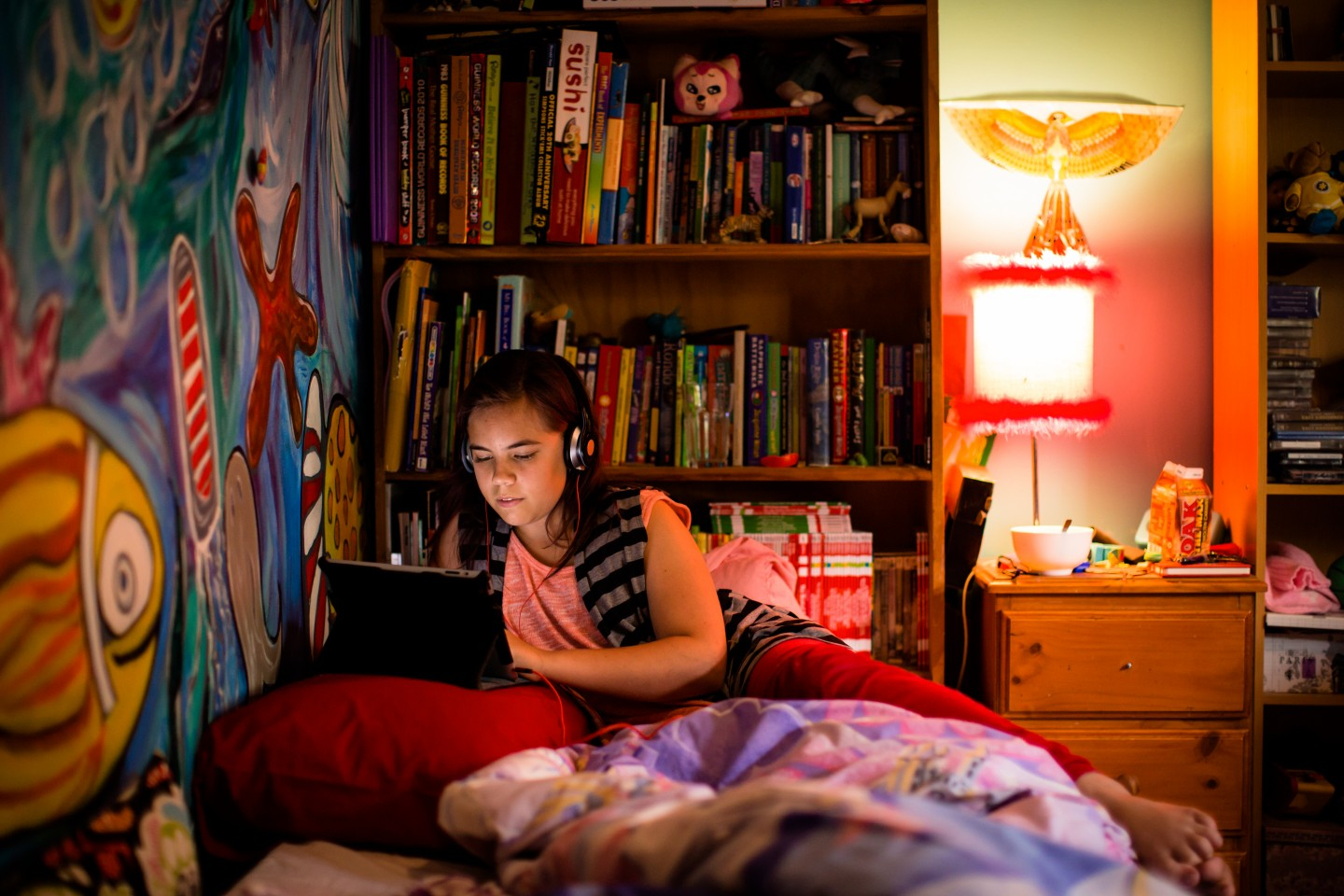 Young person on laptop in front of bookcase in bedroom.