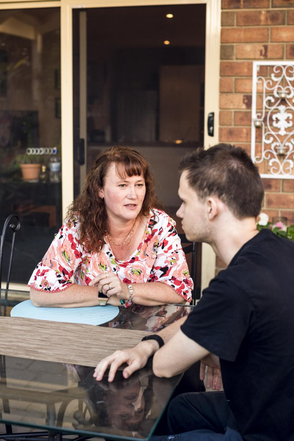 Young person having discussion with parent at garden table