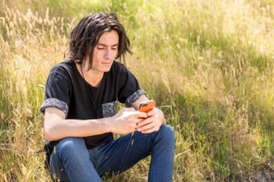 Young person sat in field on their phone