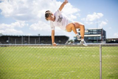 Young person leaping over fence